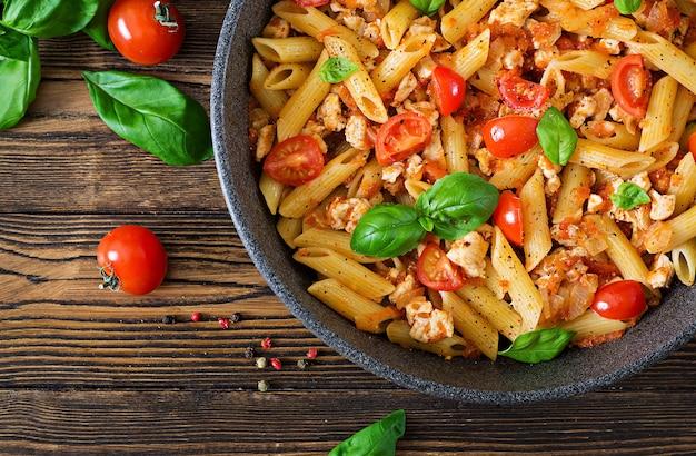Makaron penne w sosie pomidorowym z kurczakiem, pomidorami, ozdobiony bazylią na drewnianym stole. włoskie jedzenie. makaron bolognese. widok z góry. leżał płasko