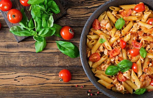 Makaron penne w sosie pomidorowym z kurczakiem, pomidorami, ozdobiony bazylią na drewnianym stole. włoskie jedzenie. makaron bolognese. widok z góry