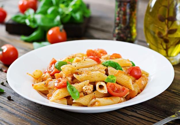 Makaron penne w sosie pomidorowym z kurczakiem, pomidorami, ozdobiony bazylią na drewnianym stole. włoskie jedzenie. makaron bolognese.