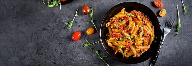 Makaron penne w sosie pomidorowym z mięsem, pomidory udekorowane kiełkami grochu na ciemnym stole.