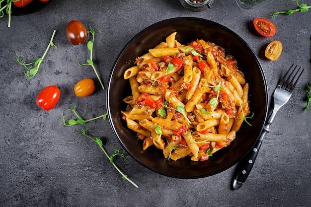 Makaron penne w sosie pomidorowym z mięsem, pomidory udekorowane kiełkami grochu na ciemnym stole