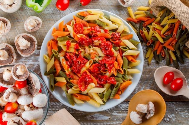 Makaron penne w talerzu z sosem, pomidorem, grzybami, pieprzem