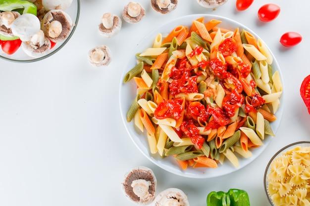 Makaron penne w talerzu z surowym makaronem, pieczarkami, pomidorem, pieprzem, sosem