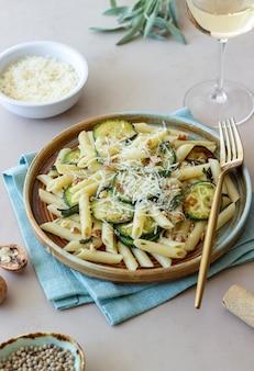 Makaron penne z cukinią, szałwią, orzechami i parmezanem. zdrowe odżywianie. jedzenie wegetariańskie. włoskie jedzenie.