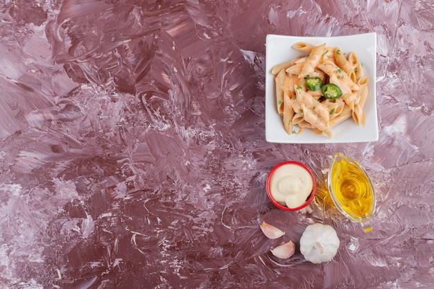 Makaron penne z majonezem i świeżym czosnkiem na lekkim stole.