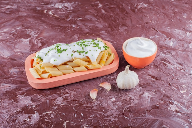 Makaron penne z majonezem i ząbkami czosnku na lekkim stole.