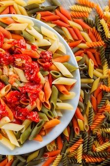 Makaron penne z sosem, pomidor w talerzu na rozproszonym makaronie