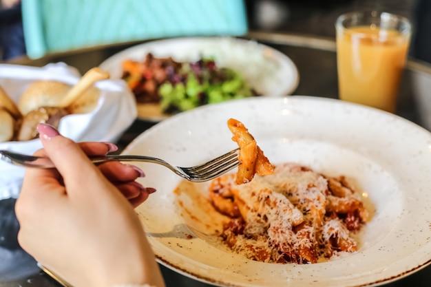 Makaron penne z sosem pomidorowym parmezanem warzywa widok z boku mięsa