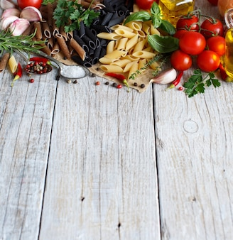 Makaron penne z warzywami, ziołami i oliwą z oliwek na drewnianym stole