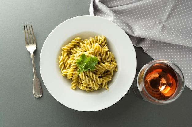 Makaron pesto i szkło różane wino w białej płytce na szarym tle. włoskie jedzenie.