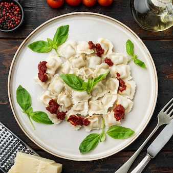 Makaron ravioli z kremowym sosem grzybowym i serem - włoskie jedzenie w stylu zestaw z bazyliowym parmezanem i pomidorem na białym talerzu na starym ciemnym drewnianym stole tle, widok z góry płasko leżał
