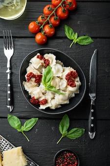 Makaron ravioli z sosem śmietanowo-grzybowym i serem włoski zestaw spożywczy z bazyliowym parmezanem i pomidorem w czarnej misce, na czarnym drewnianym stole, widok z góry na płasko