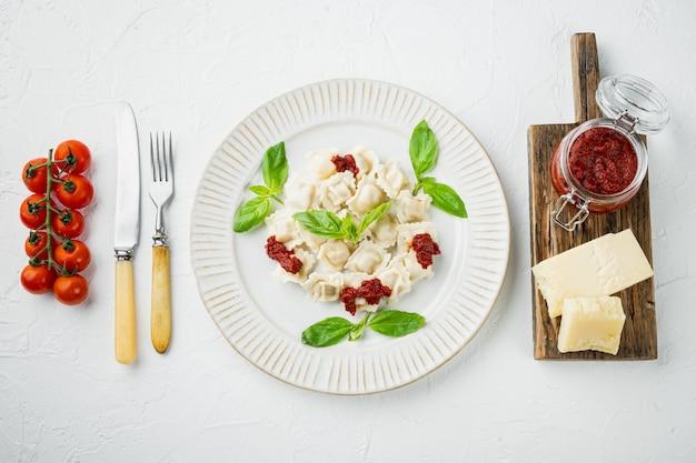 Makaron ravioli z sosem śmietanowo-grzybowym i serem - zestaw w stylu włoskim z bazyliowym parmezanem i pomidorem na białym talerzu, na białym tle, płaski widok z góry