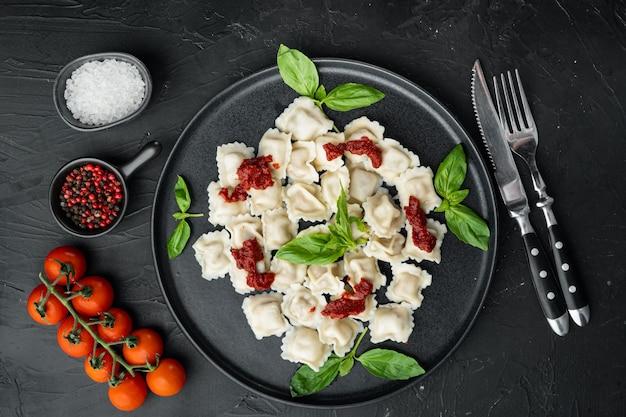 Makaron ravioli z sosem śmietanowo-grzybowym i serem - zestaw w stylu włoskim z bazyliowym parmezanem i pomidorem na czarnym talerzu, na czarnym tle, widok z góry na płasko