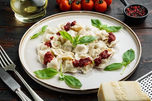 Makaron ravioli z sosem śmietanowym grzybowym i serem - włoski zestaw stylu żywności z bazyliowym parmezanem i pomidorem na białym talerzu na starym ciemnym drewnianym stole