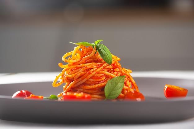 Makaron restauracyjny w sosie pomidorowym, podany na szarym talerzu. wykwintna kuchnia