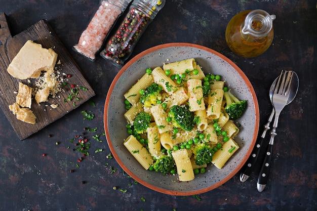 Makaron rigatoni z brokułami i zielonym groszkiem. menu wegańskie. żywność dietetyczna. leżał płasko. widok z góry.