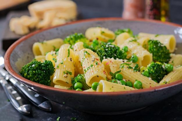 Makaron rigatoni z brokułami i zielonym groszkiem. menu wegańskie. żywność dietetyczna