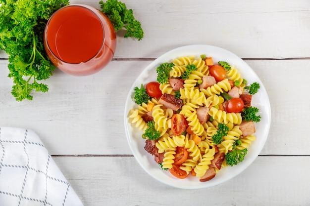 Makaron rotini, szynka i warzywa ze szklanką soku pomidorowego. zbalansowany posiłek