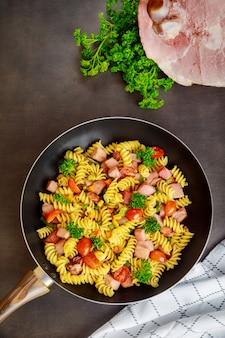 Makaron rotini z zielonym groszkiem, szynką i natką pietruszki na patelni. kuchnia włoska.