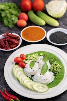 Makaron ryżowy w liściu banana z pięknie ułożonymi warzywami i dodatkami. tajskie jedzenie.
