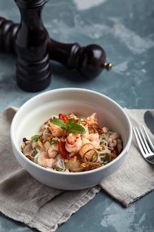 Makaron ryżowy z krewetkami i owocami morza, pikantny makaron w stylu azjatyckim w misce.