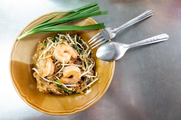 Makaron ryżowy z krewetkami i warzywami z bliska na stole. widok z góry w poziomie