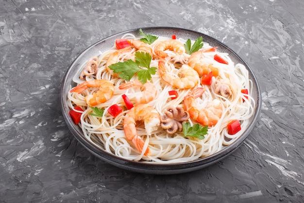 Makaron ryżowy z krewetkami lub krewetkami i małymi ośmiornicami na szarym talerzu ceramicznym na czarnym betonie. widok z boku.