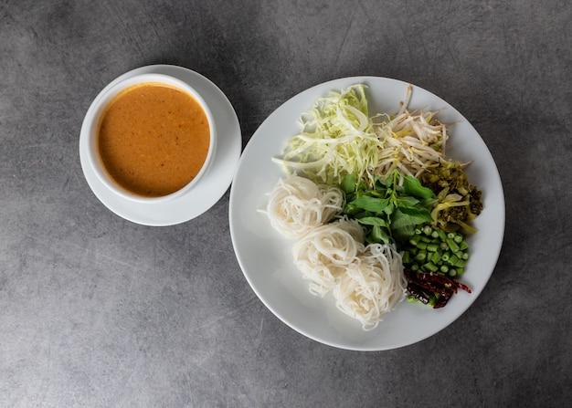 Makaron ryżowy z rybim sosem curry podawany z warzywami, kanom jeen nam ya tradycyjna kuchnia tajska