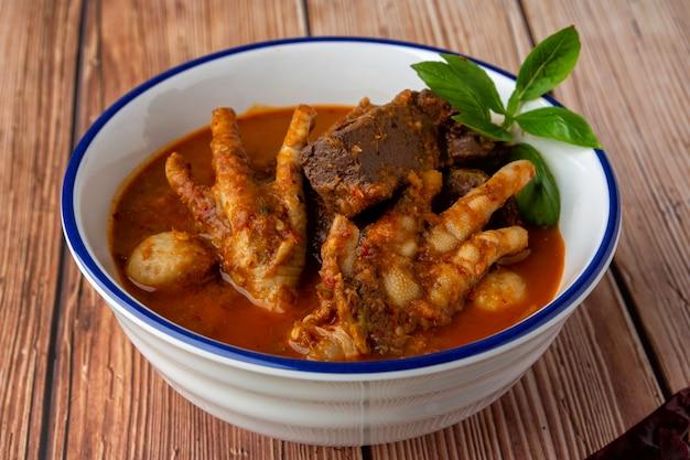 """Makaron ryżowy z sosem rybnym curry, na wierzchu klopsik, kostki krwi kurczaka, nóżki kurczaka, jajko na twardo i liście bazylii. tajskie jedzenie, tajskie nazywają to """"kanom jeen nam ya"""". udekoruj danie pięknie do podania."""