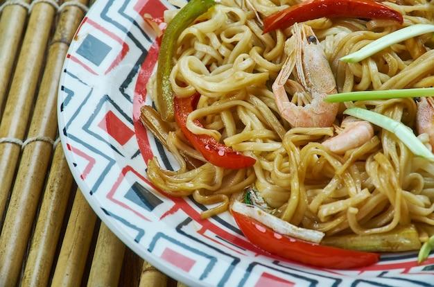 Makaron singapurski, zrobiony z cienkiego makaronu ryżowego, krewetek, krewetek. najpopularniejsze dania w chińskim menu na wynos