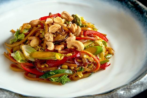 Makaron słodko-kwaśny z orzeszkami ziemnymi, warzywami i cebulą, podawany w białej misce.