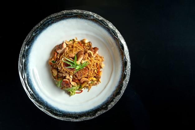 Makaron słodko-kwaśny z wieprzowiną, orzeszkami ziemnymi, warzywami i cebulą, podawany w białej misce. makaron wok.