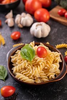 Makaron smażony z pomidorami i bazylią na szarym talerzu.