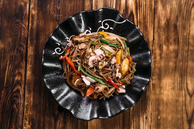 Makaron soba z owocami morza wok na czarnym talerzu
