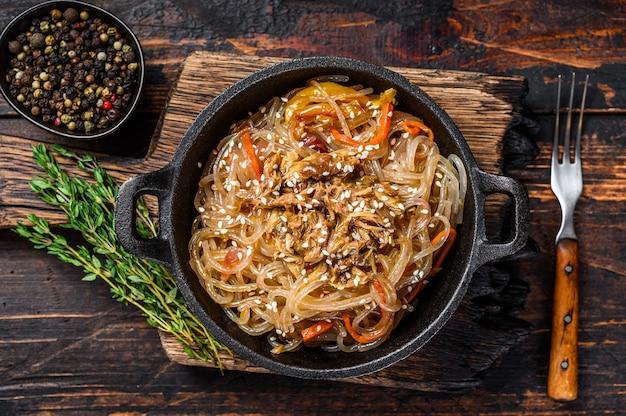 Makaron sojowy szklany z grzybami shiitake i mięsem z kurczaka. drewniany stół. widok z góry.