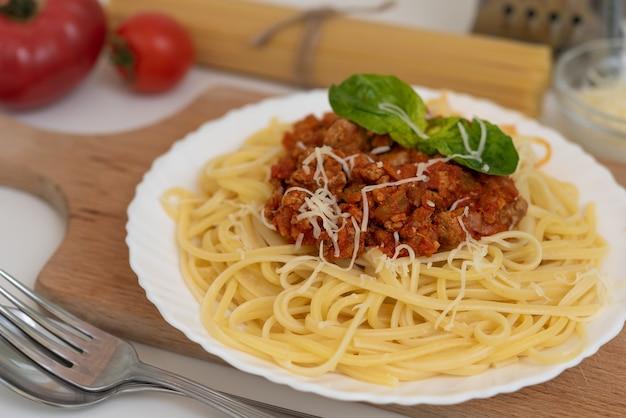 Makaron spaghetti bolognese z sosem pomidorowym, warzywami i mięsem mielonym na białym talerzu
