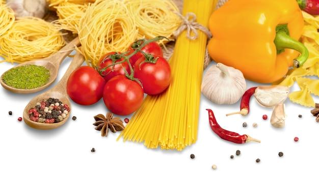 Makaron spaghetti, warzywa i przyprawy, na białym tle