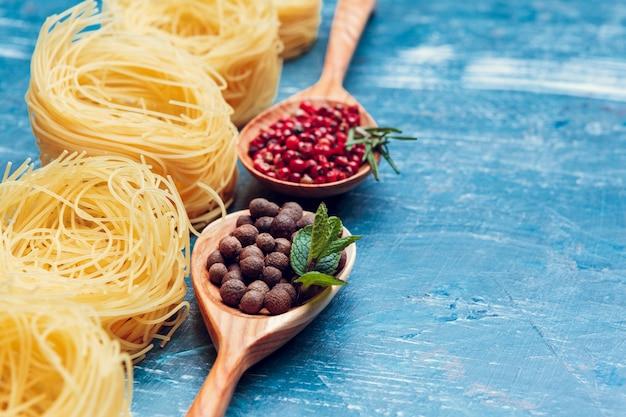 Makaron spaghetti, warzywa i przyprawy, na drewnianym stole