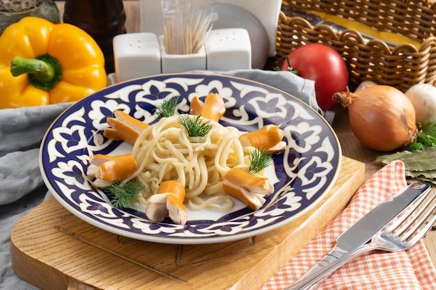 Makaron spaghetti z gotowanymi kiełbasami i koperkiem na talerzu z tradycyjnym uzbeckim