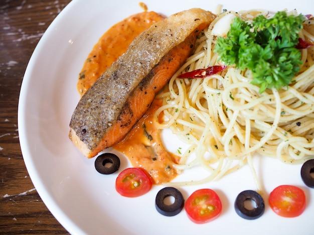 Makaron spaghetti z grillowanym łososiem i koperkiem w białym talerzu na stole żywności.