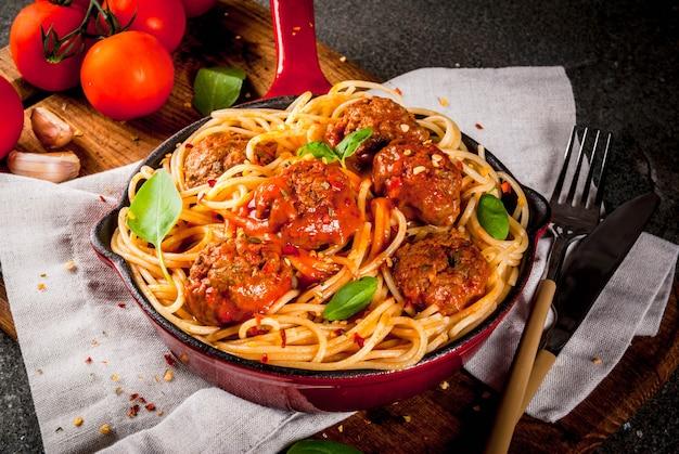 Makaron spaghetti z klopsikami, sos pomidorowy z bazylią w czerwonej żeliwnej patelni, na czarnym kamiennym stole z deską do krojenia