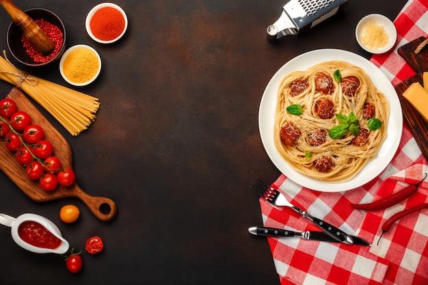 Makaron spaghetti z klopsikami, sosem pomidorowym i serem na tle zardzewiały.