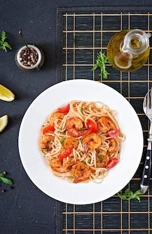 Makaron spaghetti z krewetkami, pomidorem i natką pietruszki. zdrowy posiłek. włoskie jedzenie. widok z góry. leżał płasko