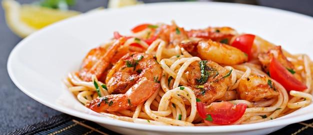 Makaron spaghetti z krewetkami, pomidorem i natką pietruszki. zdrowy posiłek. włoskie jedzenie.