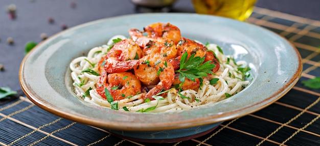 Makaron spaghetti z krewetkami, pomidorem i posiekaną natką pietruszki. zdrowe jedzenie. włoski posiłek.
