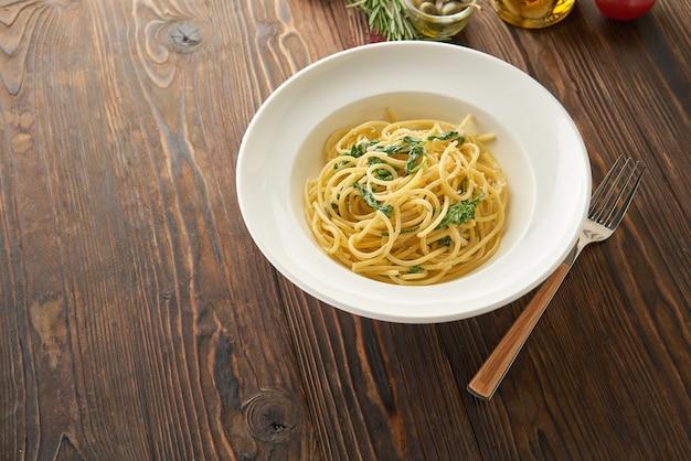 Makaron spaghetti z liśćmi szpinaku i serem na białym talerzu na drewnianym stole