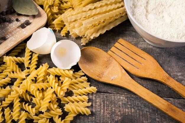 Makaron spaghetti z mąką, jajko na starym drewnianym tle