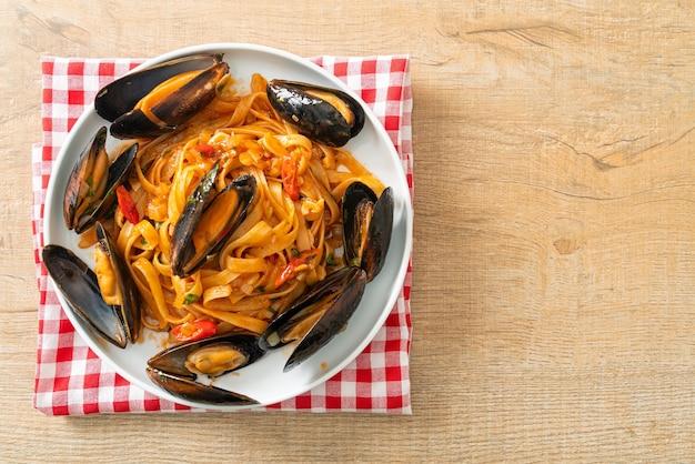 Makaron spaghetti z małżami lub małżami i sosem pomidorowym - włoskie jedzenie
