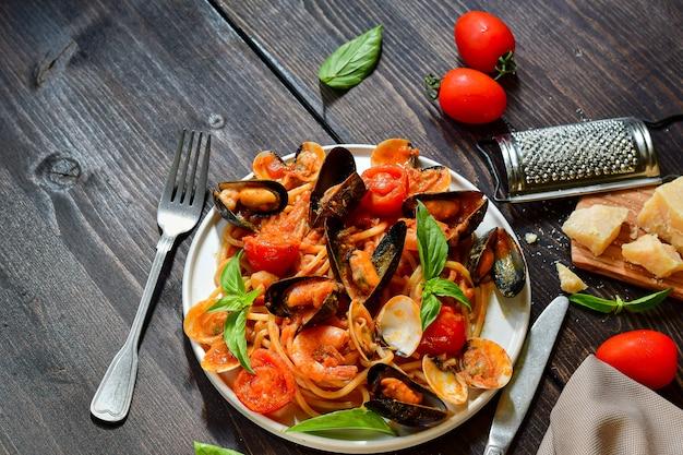 Makaron spaghetti z owocami morza z małżami i krewetkami z małżami i pomidorami w białym talerzu na drewnianym stole. przepis kuchni włoskiej. widok z góry